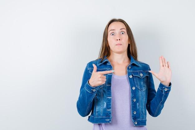 Giovane donna che indica la sua mano alzata in maglietta, giacca e sembra perplessa. vista frontale.