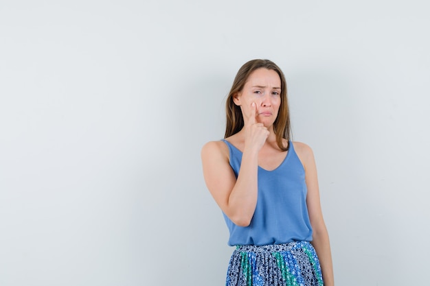 Young lady pointing at her tears in blouse,skirt and looking upset , front view. space for text