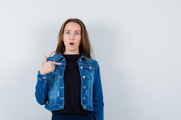 Giovane donna che indica se stessa in camicetta, giacca e sembra perplessa, vista frontale.