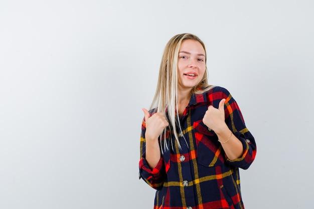 Giovane donna che punta a se stessa in camicia a quadri e sembra orgogliosa. vista frontale.