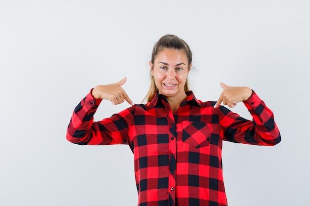 Giovane donna che punta a se stessa in camicia a quadri e sembra orgogliosa