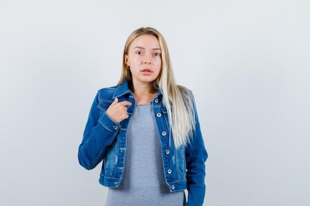 티셔츠, 데님 재킷, 치마에 자신을 가리키고 자신감을 보이는 젊은 아가씨