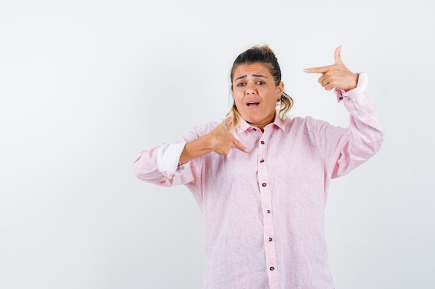 Young lady pointing at herself in pink shirt and looking anxious