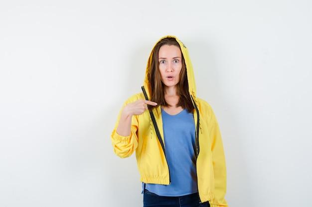 Giovane donna che indica se stessa in t-shirt, giacca e sembra perplessa, vista frontale.