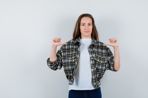 T- 셔츠, 재킷, 청바지에 엄지 손가락으로 자신을 가리키고 자랑스럽게 보이는 젊은 아가씨. 전면보기.