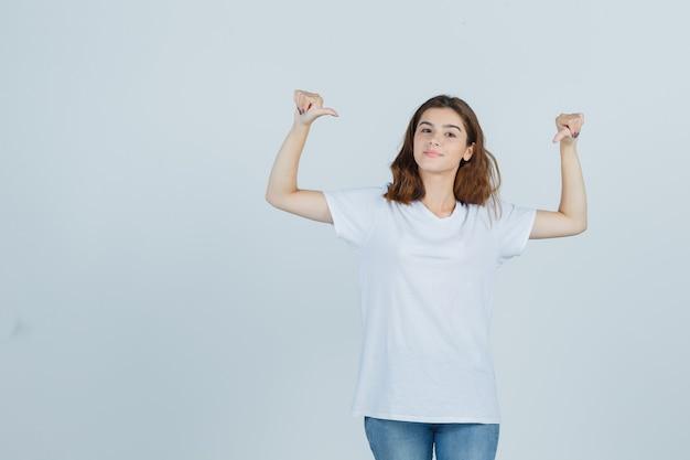젊은 아가씨 t- 셔츠, 청바지에 엄지 손가락으로 자신을 가리키는 자랑 스 러 워, 전면보기.