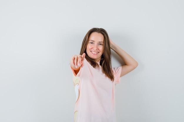 ピンクのtシャツを指差して陽気に見えるお嬢様。正面図。