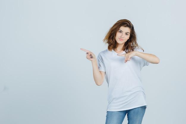 Giovane donna che punta a sinistra in t-shirt, jeans e guardando fiducioso, vista frontale.