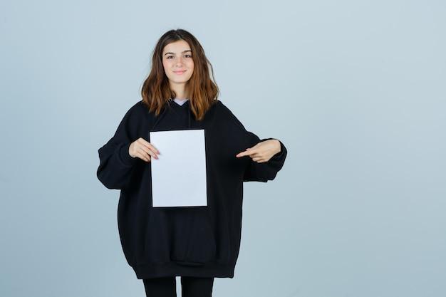 特大のパーカー、ズボンを保持し、自信を持って見ながら紙を指す若い女性。正面図。