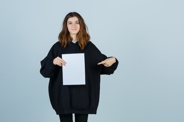 Young lady pointing paper while holding in oversized hoodie, pants and looking confident. front view.