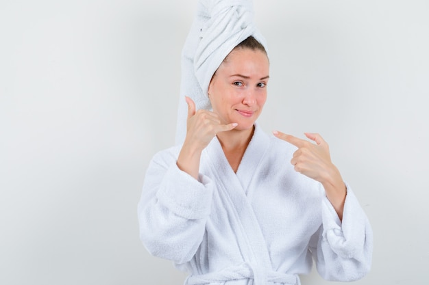 Young lady pointing at phone sign in white bathrobe, towel and looking pleased. front view.
