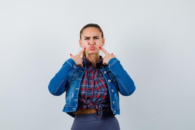 Giovane donna che indica le guance gonfie, le labbra imbronciate in camicia, giacca e sembra delusa, vista frontale.