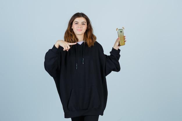 Giovane donna che indica il lato destro mentre tiene il cellulare in felpa con cappuccio oversize, pantaloni e sembra sicura di sé. vista frontale.
