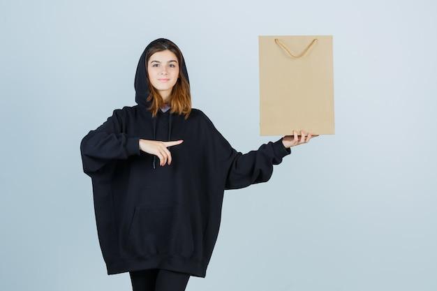 Giovane donna che indica il lato destro mentre tiene il pacchetto in felpa con cappuccio oversize, pantaloni e sembra sicura, vista frontale.