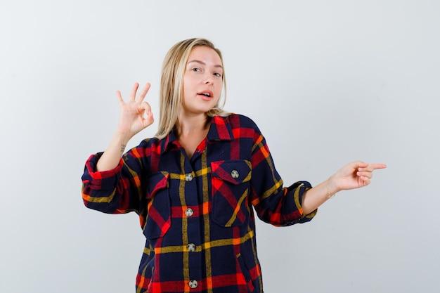 Giovane donna che indica il lato destro mentre mostra il gesto giusto in camicia a quadri e sembra felice. vista frontale.