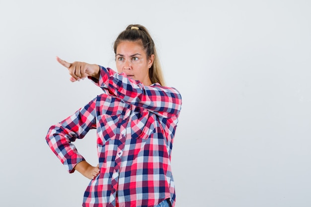 Young lady pointing at something away in checked shirt and looking angry. front view.