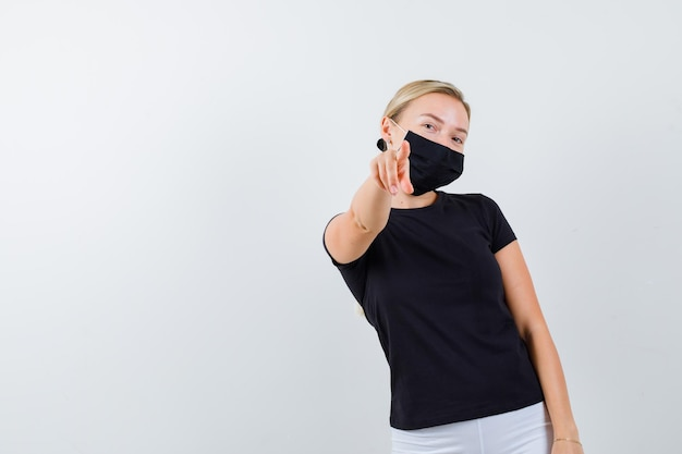 Young lady pointing in t-shirt, pants, medical mask and looking confident