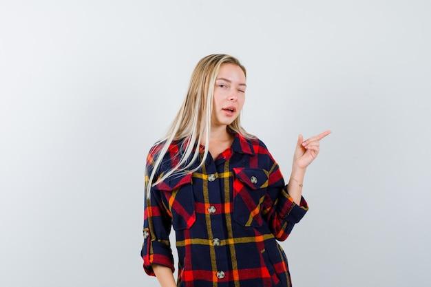 チェックシャツで右側を指して、自信を持って、正面図を探している若い女性。