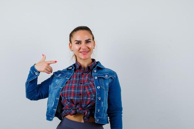 市松模様のシャツ、デニムジャケットで右側を指して陽気に見える若い女性。正面図。