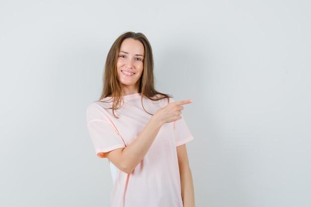 ピンクのtシャツで右側を指して自信を持って見える若い女性。正面図。