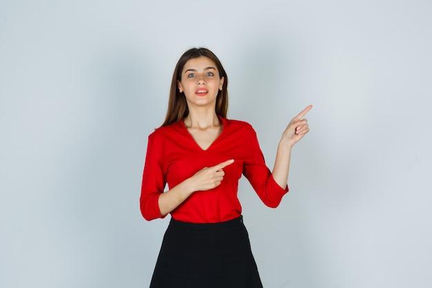Девушка в красной блузке, юбке и веселой улыбке указывает на правую сторону