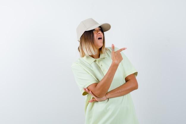 Tシャツ、キャップで右側を指して、困惑している若い女性。正面図。