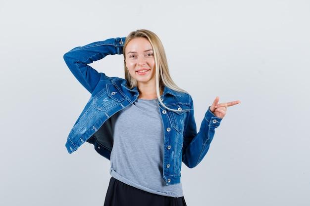 T- 셔츠, 데님 재킷, 스커트에 오른쪽을 가리키고 매혹적인 찾고 젊은 아가씨.