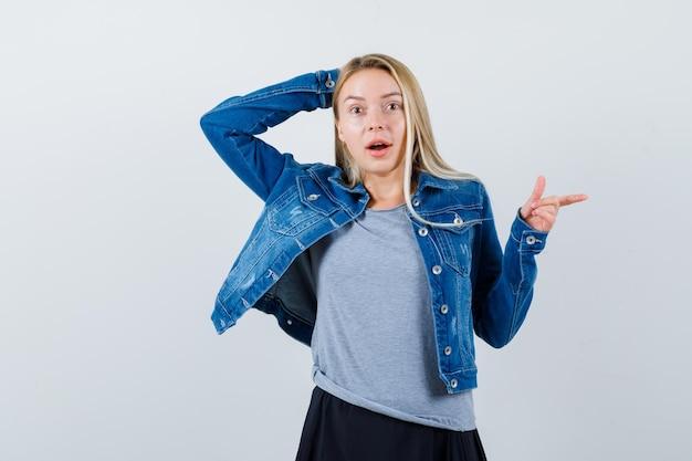 젊은 아가씨는 티셔츠, 데님 재킷, 스커트에서 오른쪽을 가리키며 놀랍습니다.