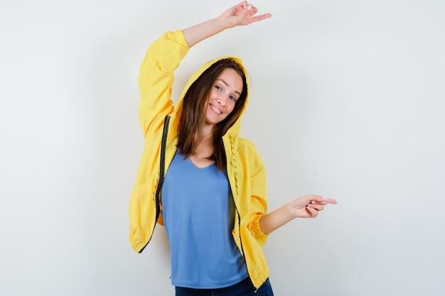 Tシャツ、ジャケット、自信を持って、正面図で右側を指している若い女性。
