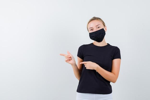 Девушка в футболке, брюках, медицинской маске, указывая на правую сторону и выглядит веселой