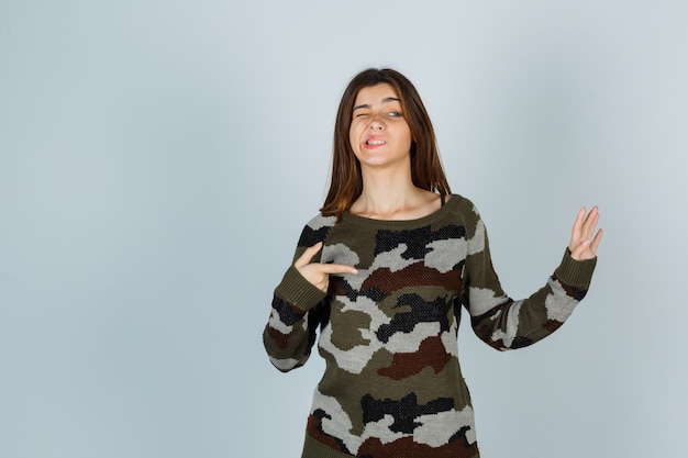 오른쪽을 가리키는 젊은 아가씨, 스웨터에 손을 들고 웃기는 찾고