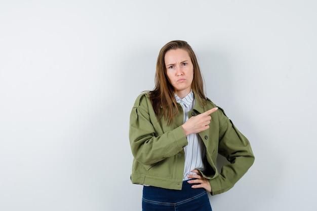 シャツ、ジャケットに眉をひそめ、躊躇しているように見えながら右側を指している若い女性。正面図。