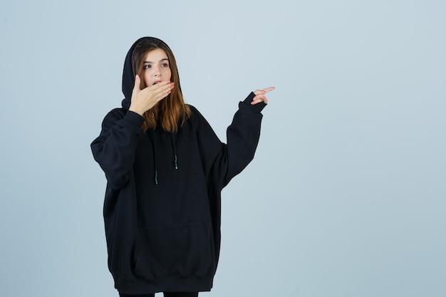 特大のパーカー、ズボンで口に手を握り、困惑しているように見える、正面図で右側を指している若い女性。