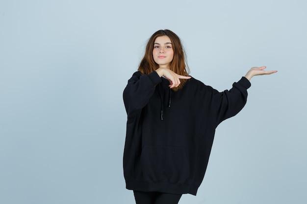 特大のパーカー、パンツで何かを見せて自信を持って見ながら右側を指している若い女性。正面図。