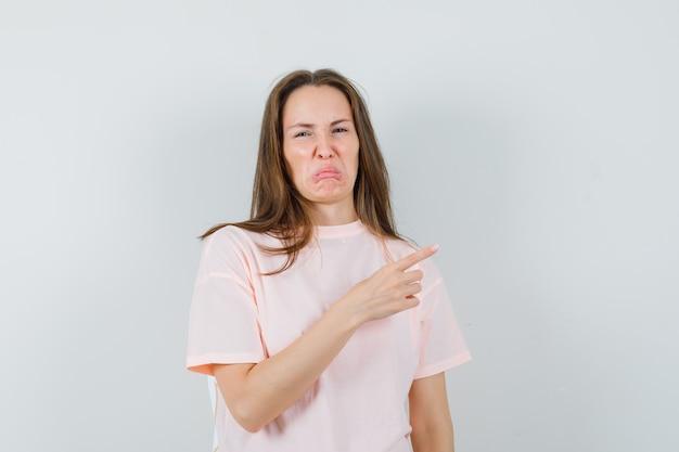 분홍색 티셔츠에 측면을 가리키고 혐오감을 느끼는 아가씨