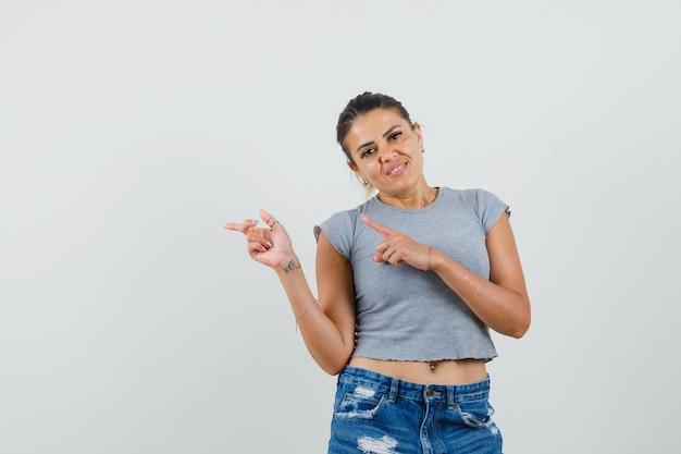 Tシャツ、ショートパンツで横を指してきれいに見える若い女性