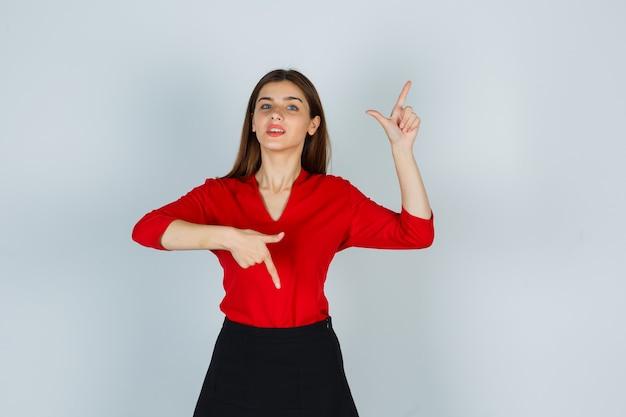 赤いブラウス、スカートで上下を指して陽気に見える若い女性