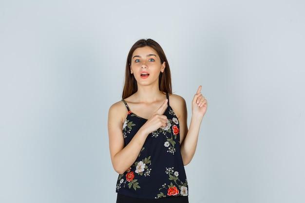 Giovane donna che indica in camicetta e sembra domandata. vista frontale.