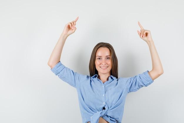 Giovane signora che indica in su in camicia blu e che sembra felice.