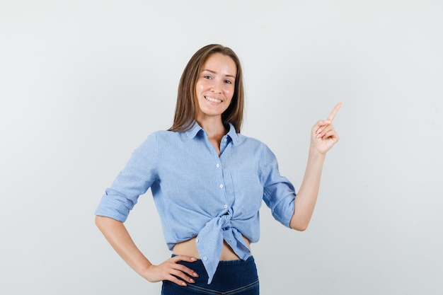 Young lady pointing up in blue shirt, pants and looking joyful.