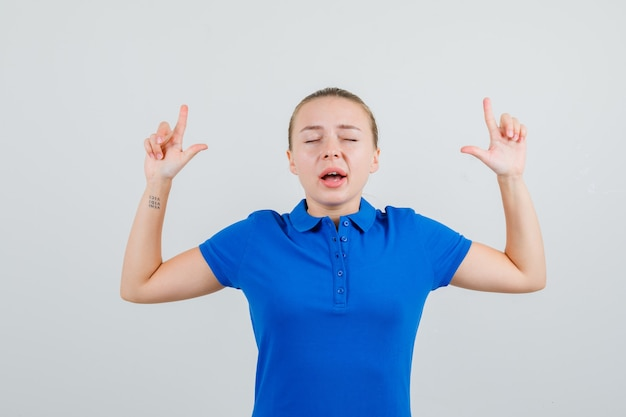 Giovane signora che indica in su in maglietta blu e che sembra speranzosa
