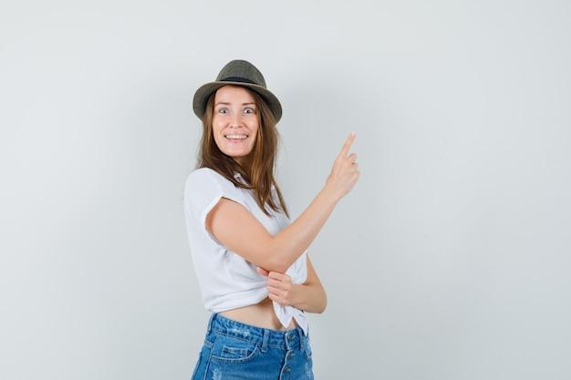 若い女性が上を向いて、tシャツ、ジーンズ、帽子からインスピレーションを得て、陽気に見える、正面図。