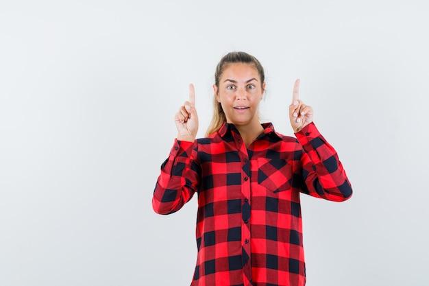Молодая леди указывая вверх в повседневной рубашке и выглядела счастливой. передний план.