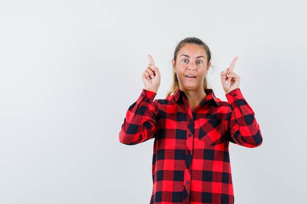 Молодая дама указывает вверх в клетчатой рубашке и выглядит удивленно