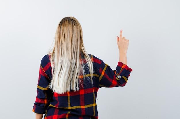 チェックのシャツを着て、自信を持って見ている若い女性、背面図。