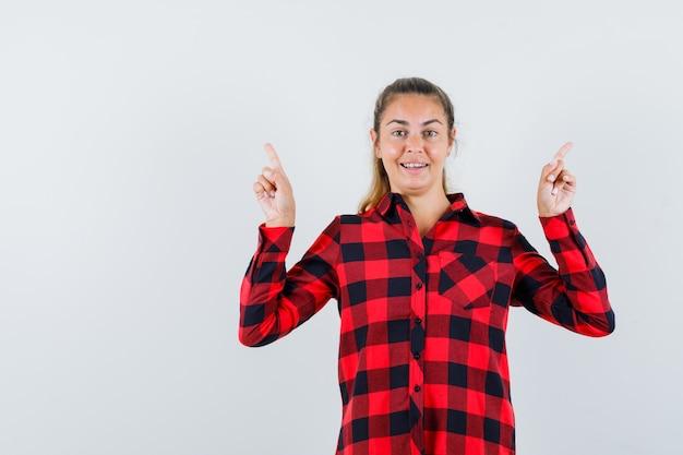 Молодая леди, указывая вверх в клетчатой рубашке и выглядя уверенно