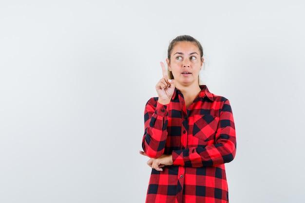 Молодая дама указывает вверх в клетчатой рубашке и смотрит задумчиво