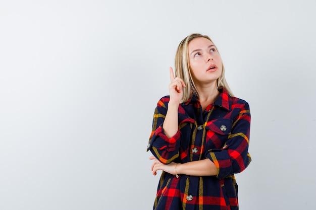 Молодая леди указывая вверх в клетчатой рубашке и глядя задумчиво. передний план.