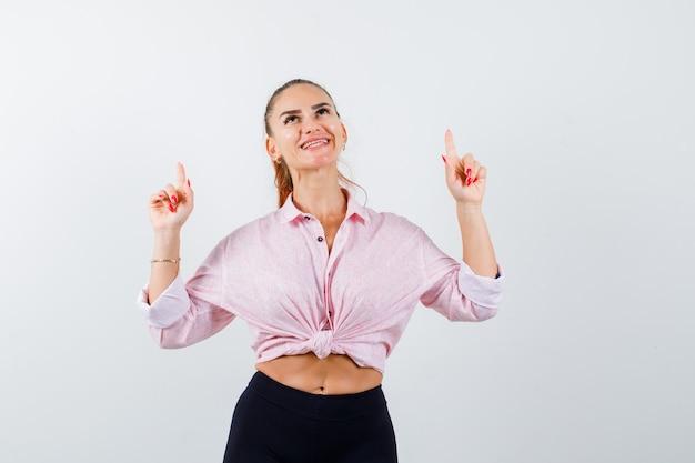 Молодая леди, указывая вверх в рубашке, штанах и радостно глядя. передний план.