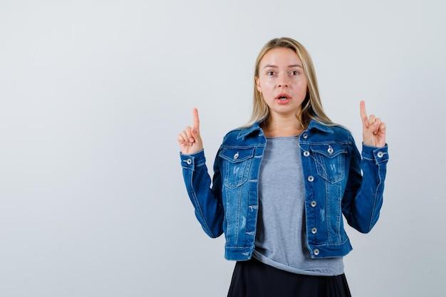 T- 셔츠, 데님 재킷, 치마를 가리키고 놀란 젊은 아가씨